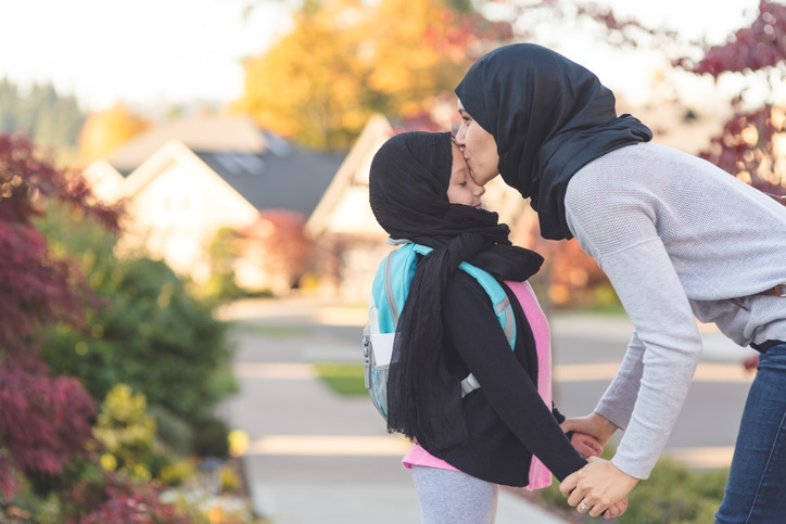 Mother in head scarf kissing daughter in head scarf