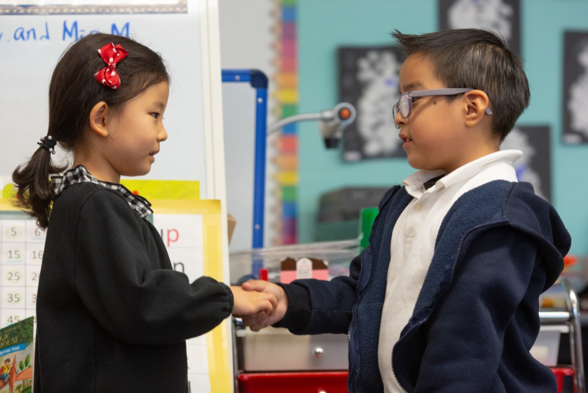 Girl and boy shaking hands in classroom