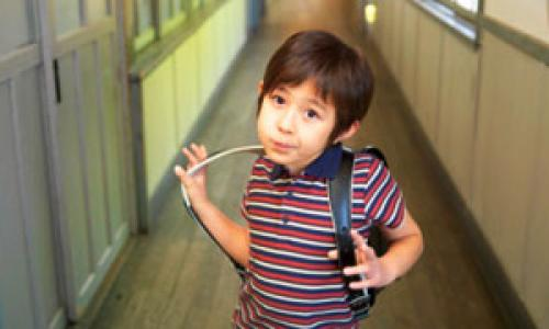 Young boy with backpack at school