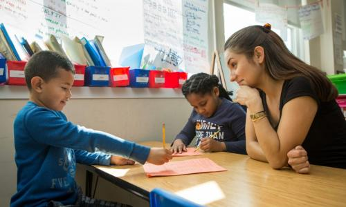 A teacher working with a boy and a girl on their writing.