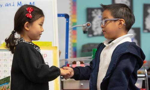 Boy and girl shaking hands in kindergarten classroom