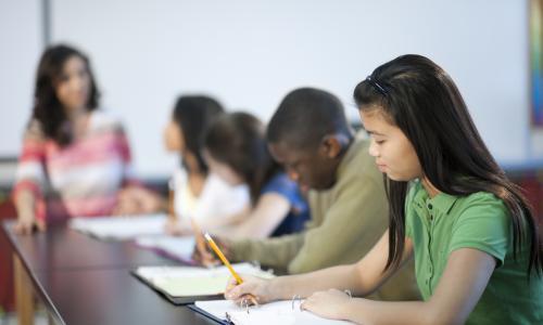 Students writing at a long table.