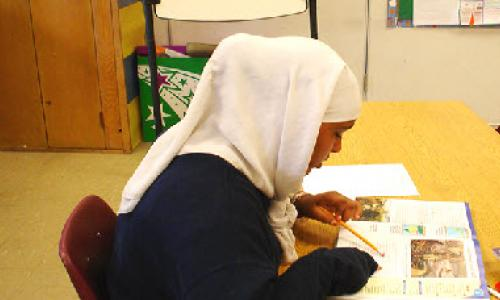 A girl in a hijab reading.