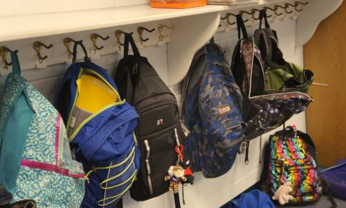 A row of haning backpacks.