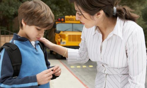 A woman talking to a sad boy in front of a school bus.