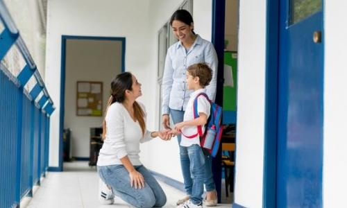 A woman on her knees talking to a boy and another woman in a school hallway.