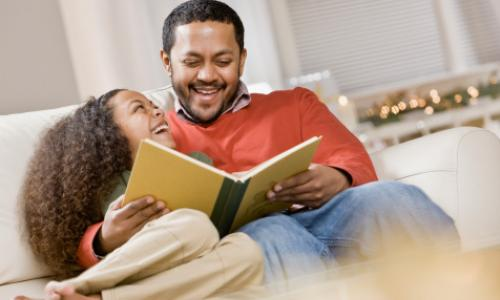 Father and daughter reading a book on couch