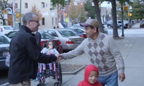 Two men shaking hands in the street with a girl in a wheelchair behind them.