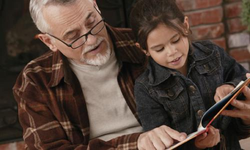 An older man reading to a young girl in his lap