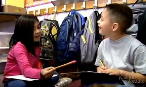 A boy and girl smiling at each other and holding pencils and paper.