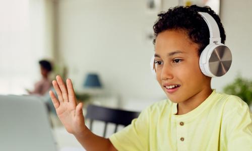 Boy waving to laptop