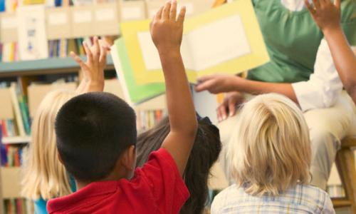 Children raising their hands in class as someone reads to them.