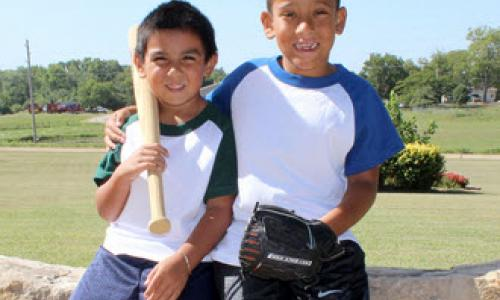 Two boys in baseball uniforms smiling at the camera.