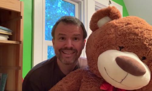 Principal Mark Gaither holding teddy bear