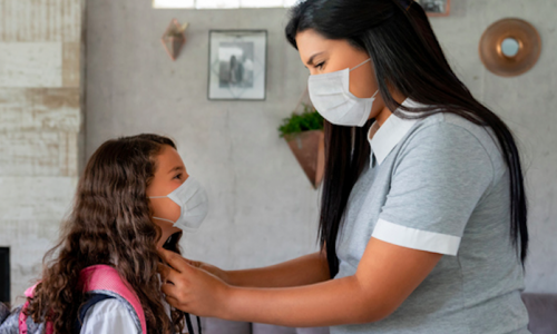 Mother saying good-bye to child before school wearing face masks