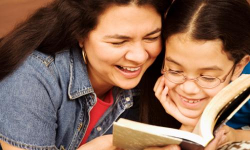 A smiling mother and daughter reading together.