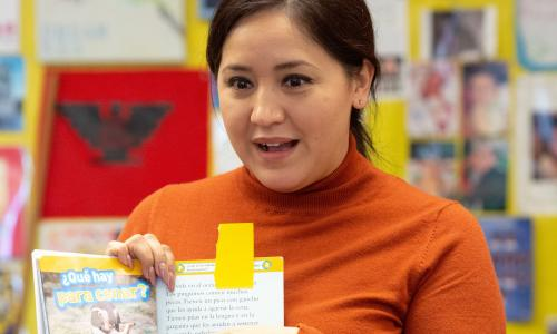 Teacher reads Spanish information about penguins