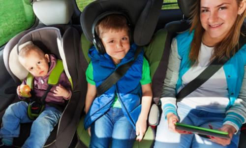 A teenager, a boy, and a baby sitting in the backseat of a car and smiling.
