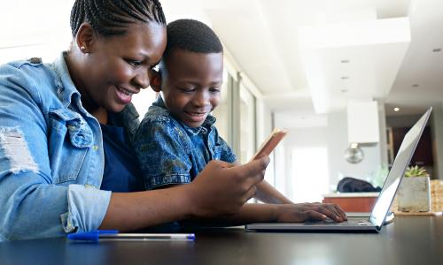 Mother looking at laptop with son