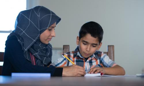 Muslim mother helping son with homework