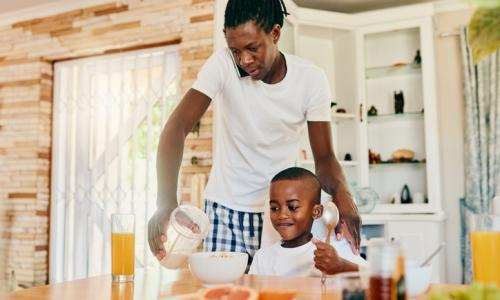 Father talking on cell phone while giving son breakfast