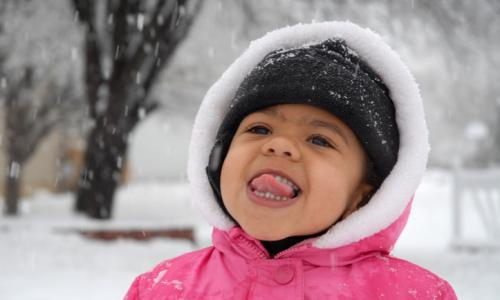 A girl sticking out her tongue in the snow.