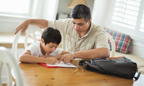 Father helping son with homework at table