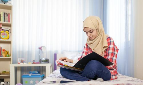 Teenage Muslim girl studying in room