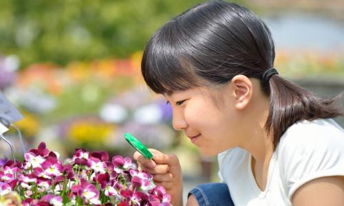 A girl looking at flowers through a magnifying glass.