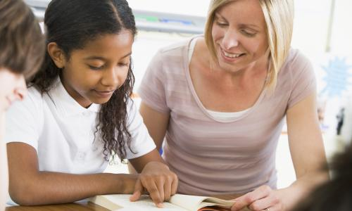 Female teacher working one-on-one with female student