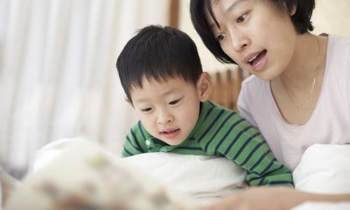 Mother and son reading together at home