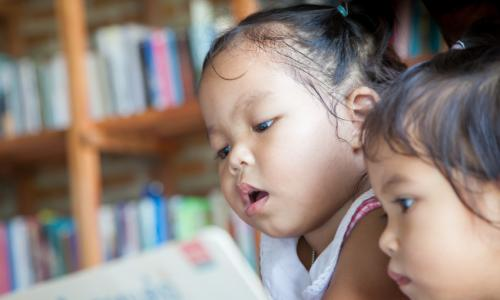 Two very young children looking at a book.
