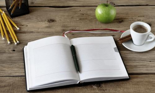 A notebook, coffee cup, pencils, and an apple on a wood table.