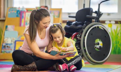 A woman sitting on the floor reading with a child and there is a wheelchair behind them.
