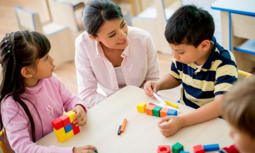 A woman smiling at two kids who are playing with blocks.