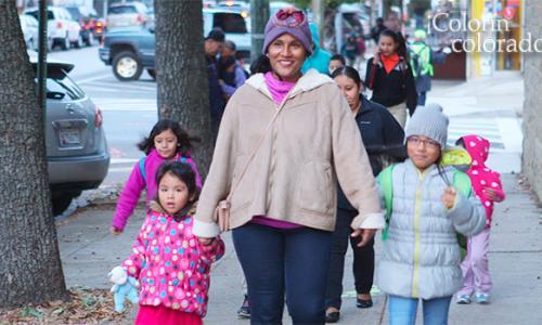 A woman walking two kids to school.
