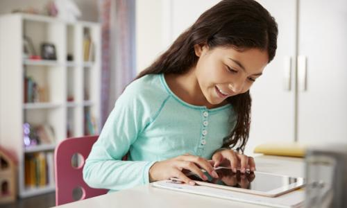 Young girl studying on laptop in room