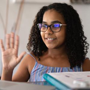 Girl waving at computer