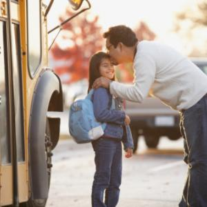 Father kissing daughter near school bus