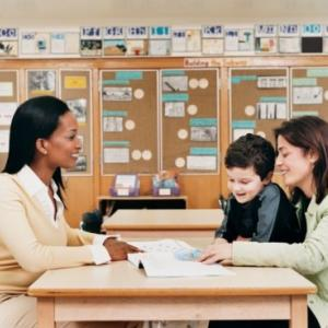 A teacher talking with a woman and boy at a classroom table.