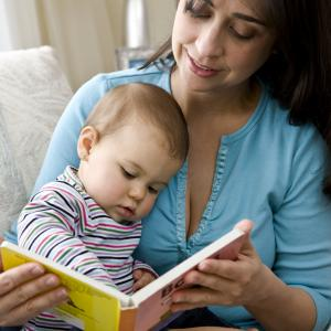 A woman reading to a baby in her lap.