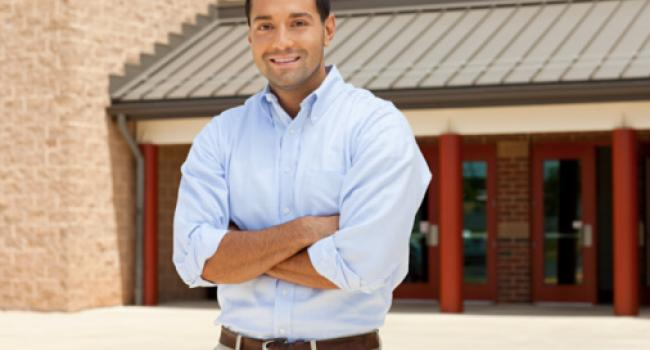 A smiling man standing in front of a school building