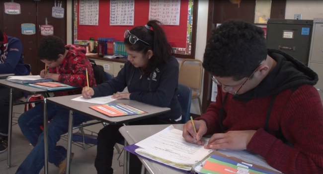 Three young adults writing at their desks