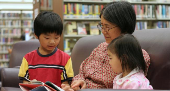 an adult and two children sitting in a library looking at a book