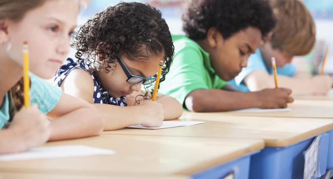 young children writing at their desks