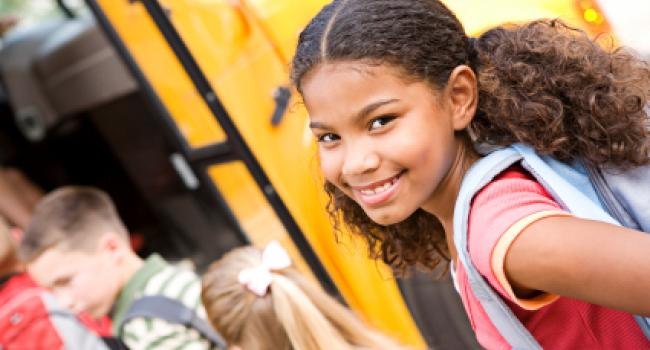 girl smiling at the camera as she gets on a school bus