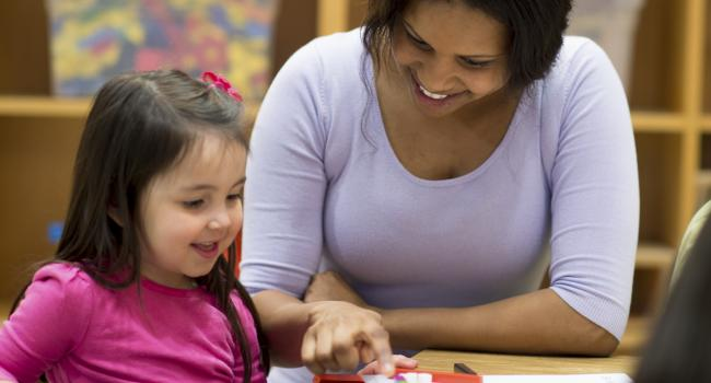 A smiling woman and child looking at something on a table.