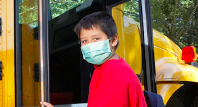 Boy in face mask getting on bus