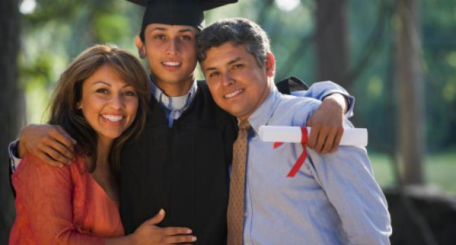 a young man in a cap and gown standing between two adults
