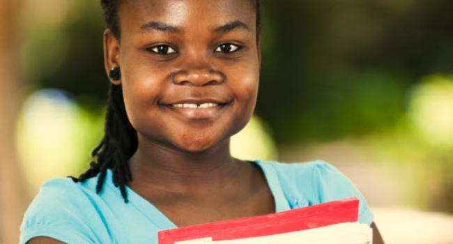 girl smiling at camera holding books